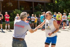 Hudson Headwater employee handing out medals at local race